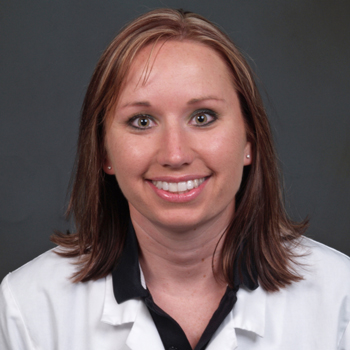 Team member Kelli wearing a white lab coat over a black polo shirt