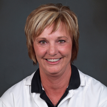 Team member Linda wearing a white lab coat over a black polo shirt