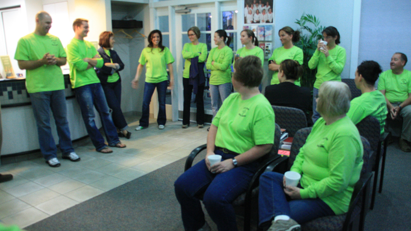 Dental team in bright green t-shirts gathered in the lobby before the start of Clay Center Family Dental Care Dental Mission day