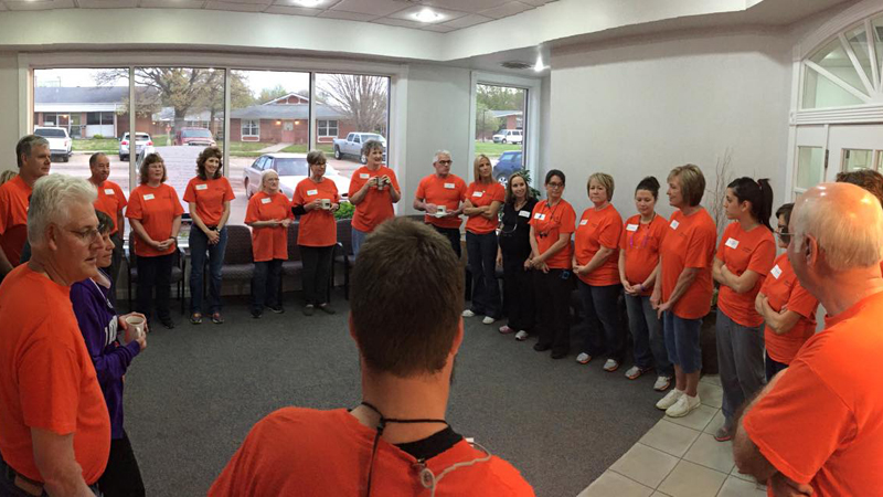 Dental team gathering in a circle in mainly orange t-shirts before the start of Clay Center Family Dental Care Dental Mission day